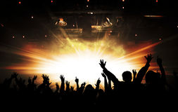 Silhouettes of concert and bright stage lights background. Hands up, toned, bright stage lights background stock images