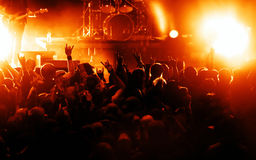 Silhouettes of concert crowd. In front of bright stage lights Stock Image