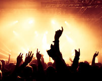 Silhouettes of concert crowd. In front of bright stage lights Stock Images