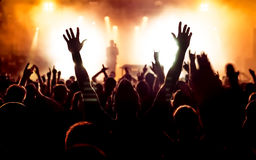 Silhouettes of concert crowd. In front of bright stage lights Royalty Free Stock Photography