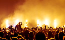 Silhouettes of concert crowd. In front of bright stage lights stock photo