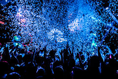 Silhouettes of concert crowd in front of bright stage lights with confetti royalty free stock images