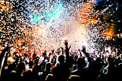 Silhouettes of concert crowd in front of bright stage lights with confetti Royalty Free Stock Image