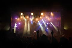 Silhouettes of concert crowd in front of bright stage lights Stock Image