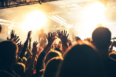 Silhouettes of people in a bright in the pop rock concert in front of the stage. Hands with gesture Horns. That rocks. Party in a. Silhouettes of hands on Stock Photography
