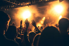Silhouettes of people in a bright in the pop rock concert in front of the stage. Hands with gesture Horns. That rocks. Party in a. Silhouettes of hands on Stock Image