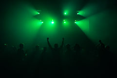 Silhouettes of people in a bright in the pop rock concert in front of the stage. Hands with gesture Horns. That rocks. Party in a. Silhouettes of hands on Royalty Free Stock Image