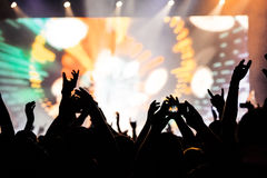 Silhouettes of concert crowd in front of bright stage lights. Silhouettes of hands on concert in front of bright stage lights stock photo