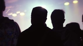 Silhouettes of concert crowd in front of bright stage lights. 1920x1080 stock footage