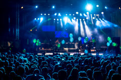 Silhouettes of concert crowd in front of bright stage lights. mo. Tion image Stock Photo
