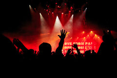 Silhouettes of concert crowd in front on bright stage lights. Peope silhouettes of rock concert crowd in front of bright stage red lights Stock Images