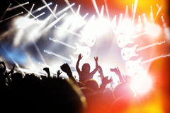 Silhouettes of concert crowd in front on bright stage lights. People black silhouettes of concert crowd in front of bright stage lights, guitar on stage Royalty Free Stock Photography