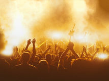 Silhouettes of concert crowd in front of bright stage lights. Royalty Free Stock Photos
