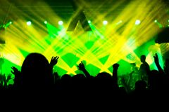 Silhouettes of the concert crowd in front of bright stage lights. Silhouettes of concert crowd in front of bright stage lights royalty free stock photos