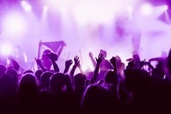 Silhouettes of the concert crowd in front of bright stage lights royalty free stock image