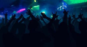 Silhouettes of concert crowd with hands raised at a music disco. Silhouettes of concert crowd with hands raised at a music festival in nightclub - disco concept Stock Images