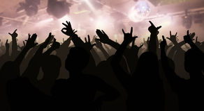Silhouettes of concert crowd with hands raised at a music disco Stock Photo