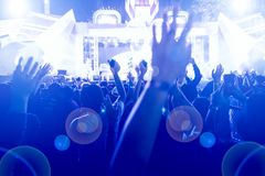 Silhouettes of concert crowd at Rear view of festival crowd rais. Ing their hands on bright stage lights Stock Image