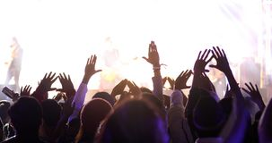 silhouettes of concert crowd at Rear view of festival crowd raising their hands on bright stage lights stock image