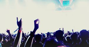 Silhouettes of concert crowd at Rear view of festival crowd raising their hands on bright stage lights.  royalty free stock photos
