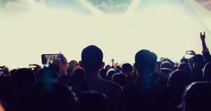 Silhouettes of concert crowd at Rear view of festival crowd raising their hands on bright stage lights royalty free stock images