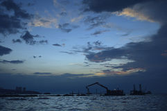 Silhouettes of construction crane at sunset in sea, Pattaya Thai Royalty Free Stock Photo