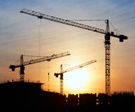 Silhouettes of construction cranes Stock Images