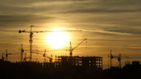 Silhouettes of construction cranes at sunset Royalty Free Stock Photography