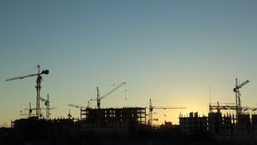 Silhouettes of construction  and power lines at Stock Photo