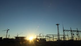 Silhouettes of construction and power lines at Royalty Free Stock Image