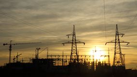 Silhouettes of construction and power lines at Stock Image