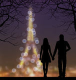 Silhouettes of couple against the Eiffel Tower and sunset sky Stock Photography