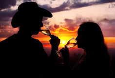 Silhouettes of couple drinking champagne at sunset Royalty Free Stock Image
