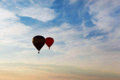 Silhouettes of couple flying balloons on the sunset sky Royalty Free Stock Photo