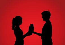 Silhouettes of couple with gift Stock Photos