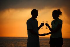 Silhouettes of couple with glasses on sunset Royalty Free Stock Photography