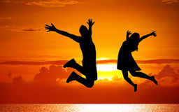 Silhouettes of couple jumping on sunset. Background Royalty Free Stock Image