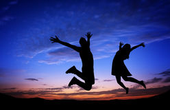Silhouettes of couple jumping when sunset Stock Photo