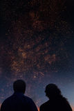 Silhouettes of couple looking at stars. Starry Stock Photos