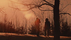 Silhouettes of couple in love, romantic landscape with sunset in winter, valentine day concept stock video footage