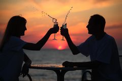 Silhouettes of couple splash with glass on sea Stock Photography