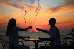 Silhouettes of couple splash out drink from glass Stock Photo