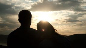 Silhouettes of a couple of young people at sunset. A woman puts her head gently on her man`s shoulder. stock video footage