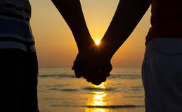 Silhouettes couples holding hands. Silhouettes couples holding hands on sunset Royalty Free Stock Images