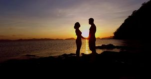 Silhouettes of couples in love. Silhouettes loving couple at sunset on the Philippine Islands stock video footage
