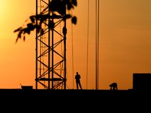Silhouettes of a crane and construction workers on a sunset background stock photo
