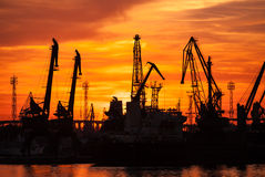 Silhouettes of cranes and cargo ships in port Royalty Free Stock Image