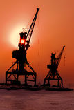 Silhouettes cranes freight ship on shore of Lake Baikal in winter at sunset. Stock Photography