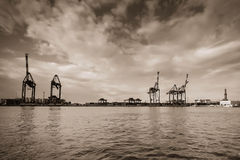 Silhouettes of cranes in harbor, sepia color. Royalty Free Stock Image