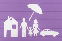 The silhouettes cut out of paper of man and woman with one girl under the umbrella, house and car near Royalty Free Stock Images